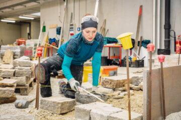 Verena: Die erste Reihe der Trockensteinmauer wird gelegt.